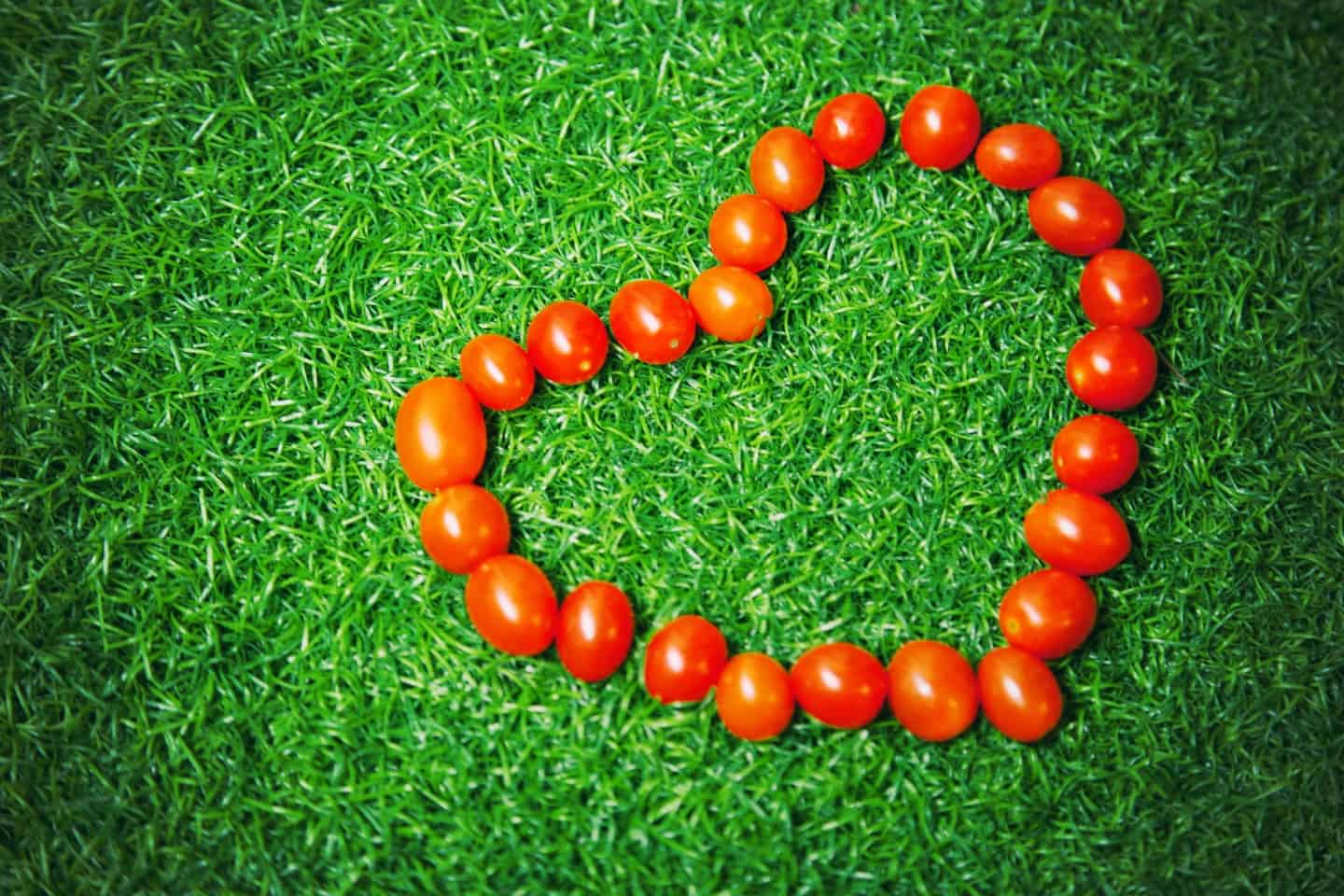 cherry tomatoes in a heart shape on grass