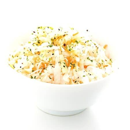 white bowl of coleslaw topped with freshly cracked black pepper
